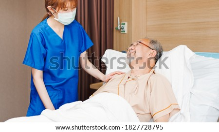 Photo of  Female Asian nurse wear mask care and check on senior male smile patient in private room in hospital bed. Nursing home, medical service, hospitality, or recovery treatment concept