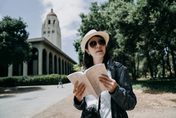 female asian student in sunglasses working and overseas study in university language learning in stanford. college girl abroad holding guided book and camera sightseeing at school in summer vacation.