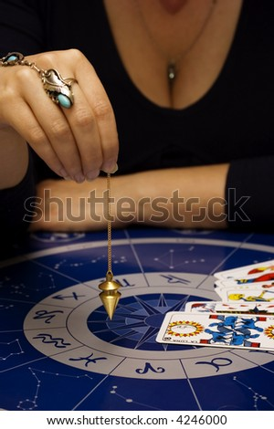 female astrologer holding a pendulum over a table with astrology chart and tarots - stock photo
