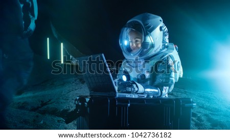Female Astronaut Wearing Space Suit Works on a Laptop, Exploring Newly Discovered Planet, Communicating with the Earth. In the Background Her Crew Member and Space Habitat. Colonization Concept. #1042736182