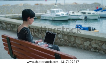 Female at the pier using computer her fingers with natural manicure typing number credit card. Caucasian young model buys via internet. Lady sitting outdoor.