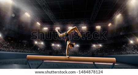 Female athlete doing a complicated exciting trick on gymnastics balance beam in a professional gym. Girl perform stunt in bright sports clothes