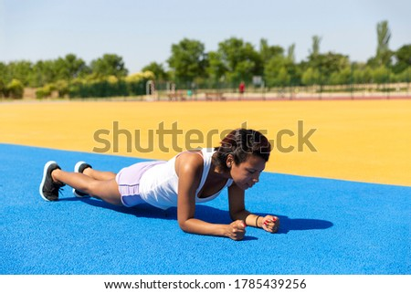 Female athlete doing abdominals in outdoor sports facilities. Space for text. Concept of sport and healthy life.