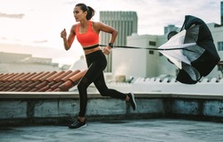 Female athlete doing drag running on rooftop. Side view of a fitness woman running on terrace of a building with a resistance parachute tied to her waist.