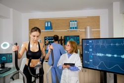 Female athlete doing physical effort on stepper and doctor with tablet in hand pursues her. Sports tests