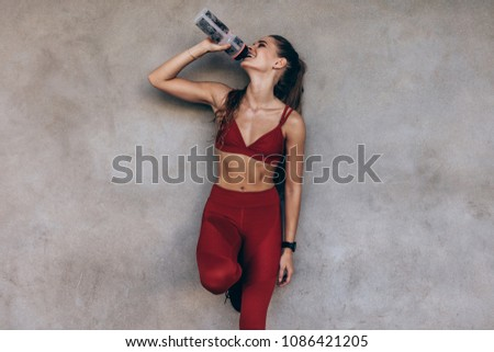 Female athlete drinking water while standing by a grey wall. Slim woman in sportswear taking a break after workout.