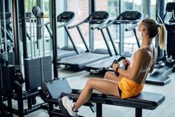 Female athlete exercising on rowing machine while wearing protective face mask in health club during coronavirus epidemic.