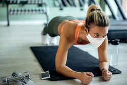 Female athlete exercising strength in plank pose while wearing protective face mask at health club.