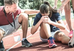 Female athlete getting injured during athletic run training - Male coach taking care on sport pupil after physical accident - Team concept with young sporty people facing mishaps casualty