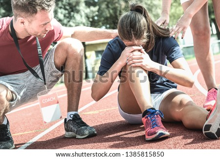 Female athlete getting injured during athletic run training - Male coach taking care on sport pupil after physical accident - Team care concept with young sporty people facing mishaps casualty #1385815850