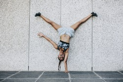 Female athlete in training clothes doing an acrobatic move turning upside down outdoors. Acrobatic fitness woman balancing upside down on one hand with legs in air.