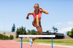 Female athlete jumping above the hurdle during the race