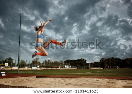 Female athlete jumping at training at stadium. The jump, athlete, action, motion, sport, success and training concept