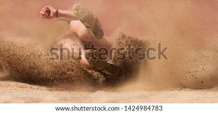 Female athlete long jump landing sand spray #1424984783