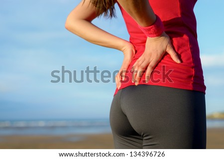 Female athlete lower back painful injury. Caucasian fitness girl gripping her lowerback because sport injury after exercising and running.