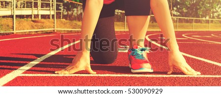 Female athlete on the starting line of a stadium track preparing for a run #530090929
