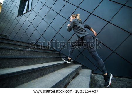 Female athlete running fast up the stairs - staircase workout