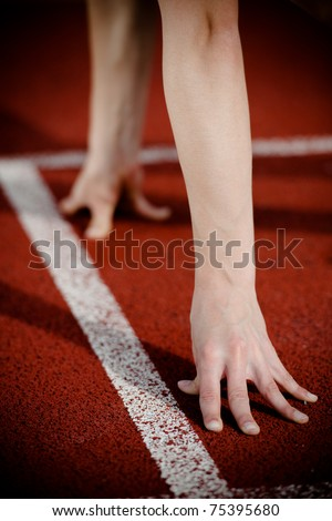 Female athlete's arms on the starting line. High contrast.