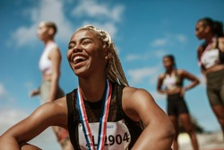 Female athlete smiling after winning a race with other competitors in background. Sportswoman with medal celebrating her victory at stadium.