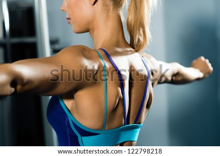 female athlete straining back muscles and arms do sport in the fitness club