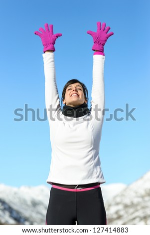 Female athlete success joyful sport concept on winter road mountain background. Happy beautiful cheerful caucasian female athlete with arms up.