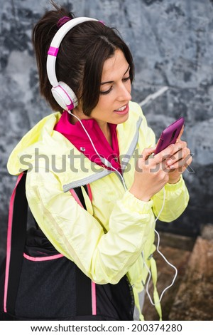 Female athlete texting sms with smartphone and relaxing after gym workout. Relaxed fitness woman leaning on a wall taking a break while looking her cellphone and listening music.