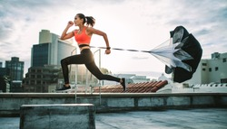 Female athlete training on terrace of a building with a parachute tied behind her. Fitness woman running hard with a drag parachute on rooftop with sun flare in the background.