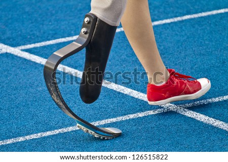 female athlete with handicap is crossing the line