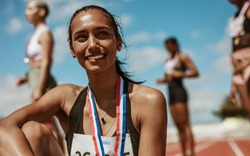 Female athlete with medal sitting on racetrack with team standing in background. Sportswoman looking away while sitting on athletics race track in stadium with her teammates in background.