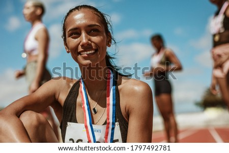 Female athlete with medal sitting on racetrack with team standing in background. Sportswoman looking away while sitting on athletics race track in stadium with her teammates in background. Foto stock ©