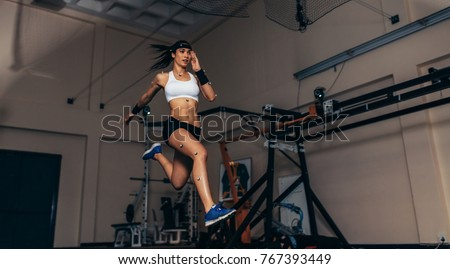 Female athlete with motion capture sensors on her body running in biomechanical lab. Recording the movement and performance of sportswoman in sports science lab.