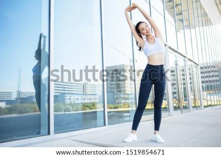 Female athlete women's sportswear fit thin physique athletic build outdoor city portrait