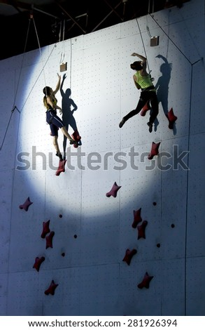 Female athletes jumping to finish point at speed climbing track in the round spotlight spot. National Climbing Championship, Dnepropetrovsk, Ukraine, May 23, 2015, Speed climbing, Female Final