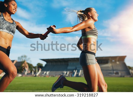 Female athletes passing over the baton while running on the track. Young women run relay race, track and field event.