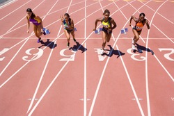 Female athletes setting off from their starting blocks at the start of a sprint race at an athletics competition at the track
