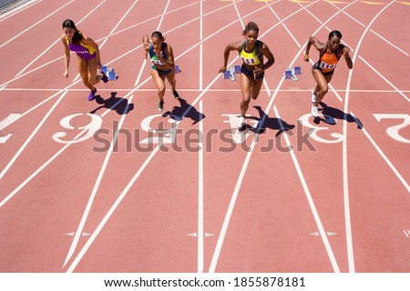 Female athletes setting off from their starting blocks at the start of a sprint race at an athletics competition at the track Foto stock ©