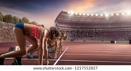 Female athletes sprinting. Three women in sport clothes on starting line prepares to run at the running track in professional stadium