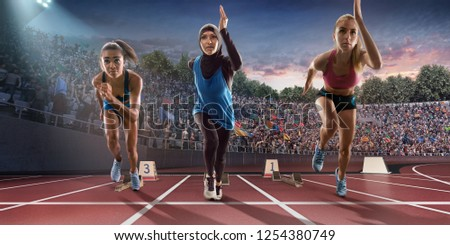 Female athletes sprinting. Women in sport clothes run at the running track in professional stadium. Muslim athlete runs in sports hijab