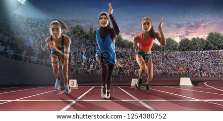 Female athletes sprinting. Women in sport clothes run at the running track in professional stadium. Muslim athlete runs in sports hijab #1254380752