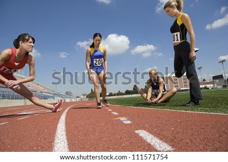 Female athletes stretching on racing track