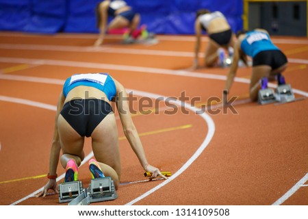 Female athletes with batons at the start in 400m relay track running
