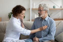 Female attending physician holding stethoscope listening old patient during homecare visit. Doctor checking heartbeat examining elder retired man at home. Seniors heart diseases, cardiology concept.
