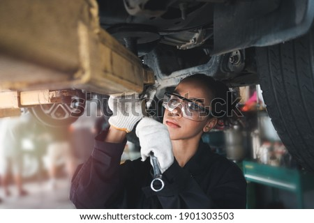 Female auto mechanic work in garage, car service technician woman check and repair customer car at automobile service center, inspecting car under body and suspension system, vehicle repair  shop.
