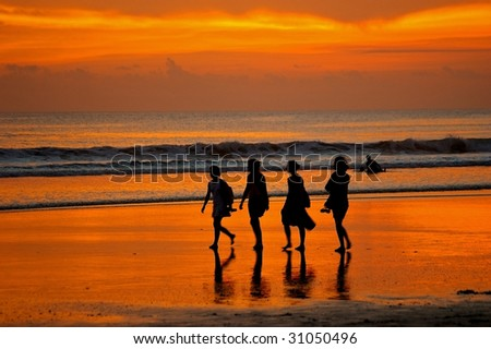 Female backpackers taking a stroll on Double Six beach, Seminyak, Bali, Indonesia.