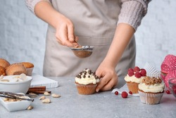 Female baker decorating tasty cupcake with cinnamon at table