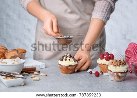 Stock Photo Female baker decorating tasty cupcake with cinnamon at table