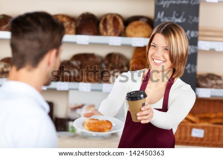 Female baker giving coffee and croissant to male customer in the bread store