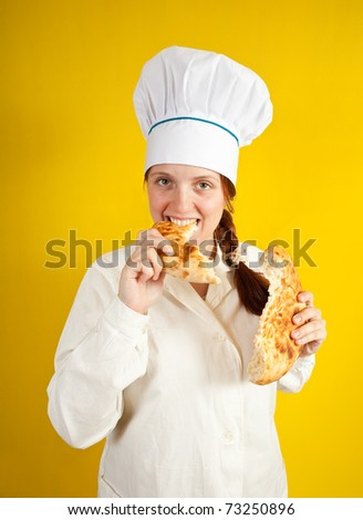 female baker is eating fresh loaf over yellow
