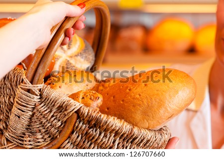 Female baker or saleswoman in her bakery with a female customer and fresh pastries or bakery products - stock photo