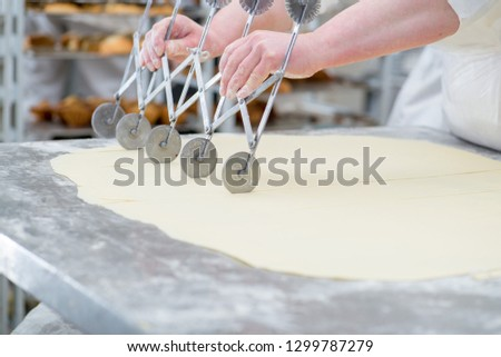 female baker's hands cut the dough into portions